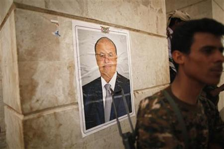 A police trooper stands guard near a poster of Yemen's President Abd-Rabbu Mansour Hadi at the gate of a local authority compound in the southern Yemeni city of Zinjibar June 21, 2012. REUTERS/Khaled Abdullah