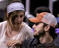 Actor Ashton Kutcher (R) chats with his girlfriend Demi Moore's daughter, Scout Willis, as they watch Phoenix Suns play Los Angeles Lakers during Game 3 of the NBA Western Conference first round playoff series in Los Angeles April 28, 2006. REUTERS/Lucy Nicholson