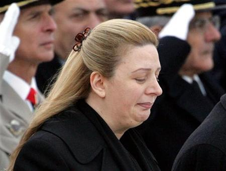 Suha Arafat waits while the coffin of her husband, Palestinian leader Yasser Arafat is loaded aboard a plane at the Villacoublay air base near Paris, November 11, 2004.