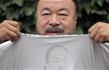 Chinese dissident artist Ai Weiwei pulls up his shirt bearing a portrait of himself as he chats with journalists at the courtyard of his studio before his verdict hearing in Beijing, July 20, 2012. REUTERS/Petar Kujundzic