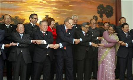 Attendees hold hands while posing for a photo before the 19th ASEAN Regional Forum (ARF) Foreign Ministers Retreat at the office of the Council of Ministers in Phnom Penh July 12, 2012. REUTERS/Samrang Pring