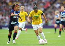 A brasileira Marta (direita) dribla a bola contra a britânica Alex Scott durante uma partida nos Jogos Olímpicos de 2012 em Londres, no Reino Unido. 31/07/2012 REUTERS/Paul Hackett