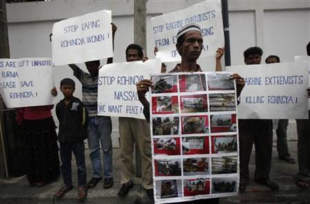 Rohingya people living in Thailand hold posters and signs as they protest in front of Myanmar's embassy in Bangkok, during Myanmar's President Thein Sein visit to Thailand July 23, 2012. REUTERS/Chaiwat Subprasom