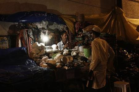 A shopkeeper (L) interacts with a customer at his illuminated shop after electricity was restored in New Delhi July 31, 2012. REUTERS/Adnan Abidi