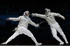 Венгр Арон Силаги (справа) в сабельном поединке против итальянца Диего Очиуззи на Олимпиаде в Лондоне 29 июля 2012 года. На Олимпийских играх в Лондоне в среду будут разыграны 20 комплектов наград. Ниже представлено расписание медальных дисциплин. REUTERS/Max Rossi