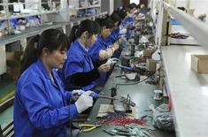 Рабочие завода электроприборов в Хэфэе, 2 мая 2012 года. Официальный индекс менеджеров по закупкам (PMI) для производственного сектора Китая упал в июле до восьмимесячного минимума 50,1 пункта, свидетельствуя, что активность едва растет. REUTERS/Stringer