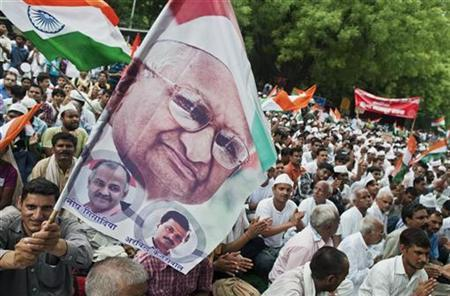 A supporter waves a flag containing a portrait of veteran social activist Anna Hazare (top), during a protest in New Delhi July 25, 2012. REUTERS/Ahmad Masood