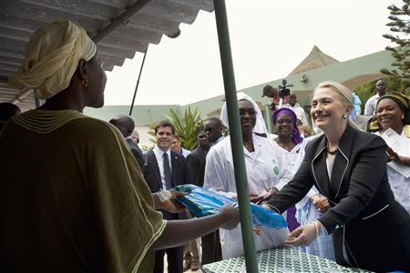 U.S. Secretary of State Hillary Clinton (R) gives a mosquito net for malaria prevention to a local woman during a tour of the Philippe Senghor Health Center in Dakar August 1, 2012. REUTERS/Jacquelyn Martin/Pool