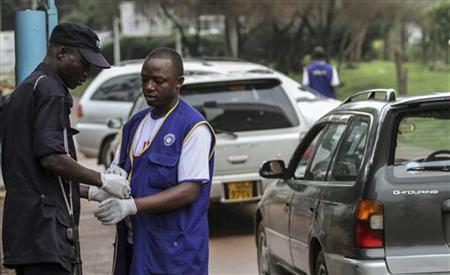 Security personnel wear gloves to check motorists entering and exiting Mulago hospital in Uganda's capital of Kampala July 31, 2012. REUTERS/Edward Echwalu