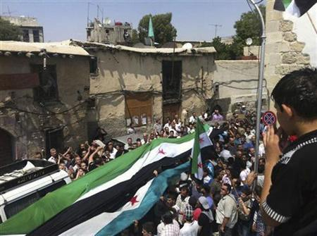 Residents hold an opposition flag during the funeral of Muhammad Al Nenin, whom activists say was killed by forces loyal to Syria's President Bashar Al-Assad, during his funeral at Al-Shaghour in central Damascus August 1, 2012. REUTERS/Shaam News Network/Handout