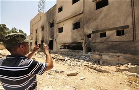 A man takes a picture of the damage to the Libyan intelligence building after a bomb explosion, in Benghazi August 1, 2012. The building had been abandoned and there were no casualties. REUTERS/Esam Al-Fetori
