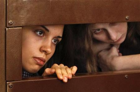 Nadezhda Tolokonnikova (L) and Maria Alyokhina, members of female punk band ''Pussy Riot'', look out from the defendent's cell in a courtroom in Moscow July 30, 2012. REUTERS/Maxim Shemetov
