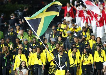 Jamaica's flag bearer Usain Bolt holds the national flag as he leads the contingent in the athletes parade during the opening ceremony of the London 2012 Olympic Games at the Olympic Stadium July 27, 2012. REUTERS/Mike Blake