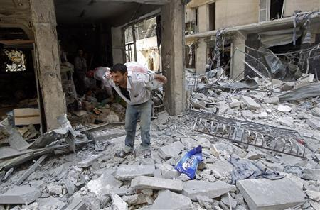 A man carries belongings from his shop destroyed by shelling from forces loyal to Syrian President Bashar Al-Assad in downtown Aleppo August 1, 2012. REUTERS/Goran Tomasevic