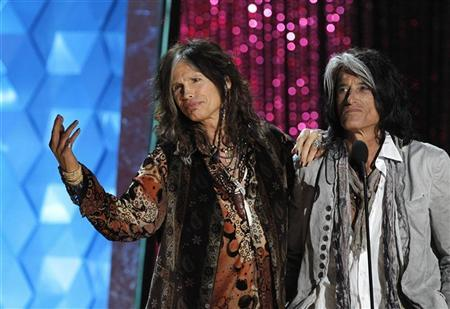 Steven Tyler (L) and Joe Perry of Aerosmith take the stage to introduce actor Johnny Depp, recipient of the MTV Generation Award, at the 2012 MTV Movie Awards in Los Angeles, June 3, 2012. REUTERS/Mario Anzuoni