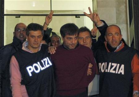 Italian policemen escort Camorra boss Antonio Iovine (C) as he leaves the police headquarters in Naples November 17, 2010. REUTERS/Ciro De Luca