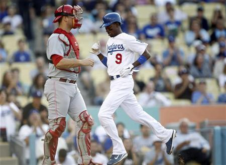 Los Angeles Dodgers' Dee Gordon (R) scores on a single by Dodgers' Luis Cruz (not pictured) with Cincinnati Reds catcher Devin Mesoraco (L) looking on during the first inning of their MLB baseball game in Los Angeles, California July 4, 2012. REUTERS/Alex Gallardo