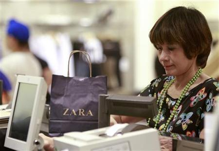 A woman pays for goods at a Zara shop in Siam Paragon shopping mall in Bangkok June 29, 2011. REUTERS/Chaiwat Subprasom/Files