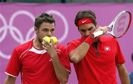 Switzerland's Roger Federer (R) and Stanislas Wawrinka confer during their men's doubles tennis match against Israel's Andy Ram and Jonathan Erlich at the All England Lawn Tennis Club during the London 2012 Olympic Games August 1, 2012. REUTERS/Stefan Wermuth