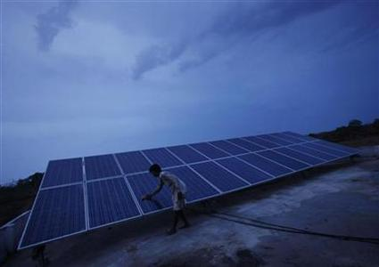 A man cleans panels installed at a solar plant at Meerwada village of Guna district in the central Indian state of Madhya Pradesh June 18, 2012. Life in the remote Indian village of Meerwada used to grind to a standstill as darkness descended. Workers downed tools, kids strained to see their school books under the faint glow of aged kerosene lamps and adults struggled to carry out the most basic of household chores. The arrival of solar power last year has changed all that. On a humid evening splashed with rain, fans whirr, children sit cross-legged to swat up on their Hindi and delighted people can actually see what they are eating and drinking. REUTERS/Adnan Abidi