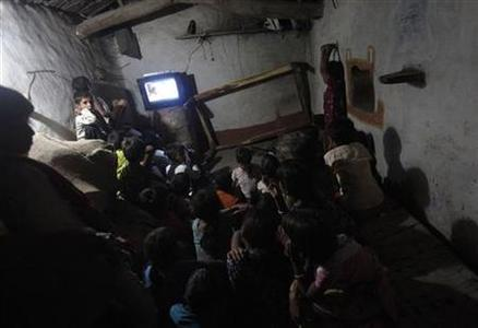 Children watch television powered by solar energy at Meerwada village of Guna district in the central Indian state of Madhya Pradesh June 18, 2012. REUTERS-Adnan Abidi