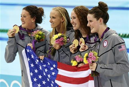 The U.S. women's 4x200m freestyle relay team hold their gold medals and national flag during the women's 4x200m freestyle relay victory ceremony at the London 2012 Olympic Games at the Aquatics Centre August 1, 2012. REUTERS/Tim Wimborne