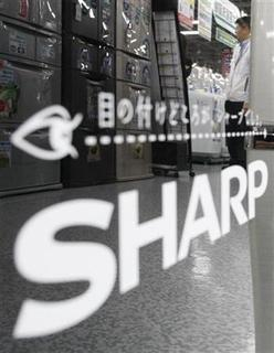 A man is reflected on Sharp's logo on its fridge at an electronic shop in Tokyo October 29, 2009. REUTERS/Kim Kyung-Hoon
