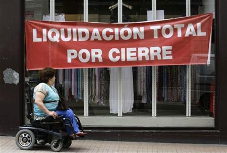A woman in a wheelchair passes the shop window of a clothing store in Pontevedra, northern Spain, June 29, 2012.REUTERS/Miguel Vidal