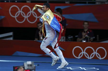 Venezuela's Ruben Limardo Gascon runs with his national flag as he celebrates winning against Norway's Bartosz Piasecki after their men's epee individual gold medal fencing match at the ExCel venue at the London 2012 Olympic Games August 1, 2012. REUTERS/Damir Sagolj