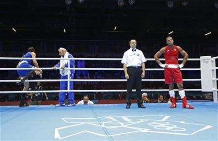 Iran's Ali Mazaheri (L) leaves the ring before the decision after being disqualified during his Men's Heavy (91kg) Round of 16 boxing match against Jose Larduet Gomez (R) of Cuba at the London 2012 Olympic Games August 1, 2012. REUTERS/Murad Sezer