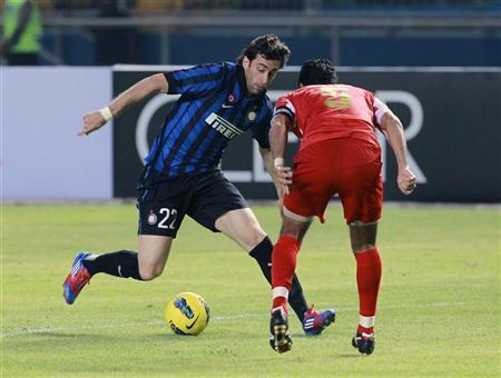 Diego Milito (L) of Italy's Inter Milan fights for the ball with Indonesia Selection FC's Putra during their international friendly soccer match in Jakarta May 24, 2012. REUTERS/Beawiharta