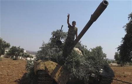 A member of the Free Syrian Army flashes the victory sign on a captured tank after taking control of a checkpoint from government forces in Anadan, north Aleppo, July 31, 2012. REUTERS/Obeida Al Naimi