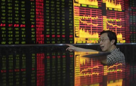 An investor gestures as he talks in front of an electronic board showing stock information at a brokerage house in Wuhan, Hubei province July 5, 2012. REUTERS/Stringer