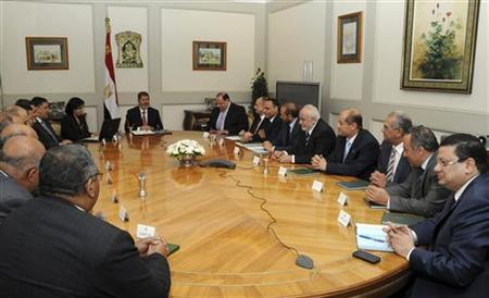 Egypt's President Mohamed Mursi (C) meets with Water Minister Hisham Kandil at the presidential palace in Cairo July 22, 2012. REUTERS/Egyptian Presidency/Handout