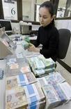 Кассир пересчитывает казахстанские тенге в отделении Казкоммерцбанка в Алма-Ате в феврале 2010 года. Национальный банк Казахстана в четверг в четвертый раз менее чем за полгода снизил ставку рефинансирования до исторического минимума - на 0,5 процентного пункта до 5,5 процента годовых вслед за замедлением потребительских цен. REUTERS/Shamil Zhumatov