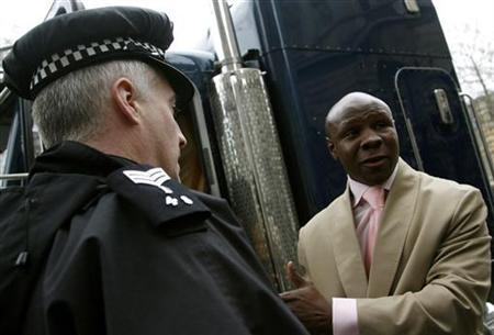 Former British world champion boxer Chris Eubank (R) argues with a policeman whilst staging a protest against sending Prince Harry to Iraq by parking his customised truck outside Downing Street in London March 29, 2007. REUTERS/Alessia Pierdomenico