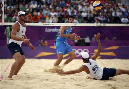 Brazil's Emanuel Rego (R) and Alison Cerutti (L) defend against Italy's Paolo Nicolai during their men's preliminary round beach volleyball match at Horse Guards Parade during the London 2012 Olympic Games August 2, 2012. REUTERS/Marcelo del Pozo