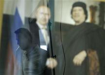 Оппозиционный лидер Алексей Навальный отражается в стекле, за которым фотография президента России Владимира Путина и бывшего ливийского лидера Муаммара Каддафи; снимок Навального сделан во время интервью в его офисе в Москве 1 августа 2012 года. Лидеры ставших поводом для массовых задержаний и обысков московских уличных протестов предупредили о новых выступлениях и забастовках осенью в ответ на то, что они считают целенаправленной кампанией Кремля по удушению гражданского движения. REUTERS/Sergei Karpukhin