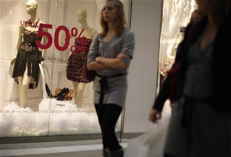 A shopper walks past a boutique advertising 50 per cent off merchandise during ''Black Friday'' at a high-end shopping mall in Tysons Corner, Virginia, November 26, 2010. REUTERS/Jason Reed