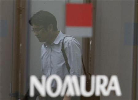 A man is reflected in a window outside a Nomura Securities branch in Tokyo June 25, 2012. REUTERS/Yuriko Nakao