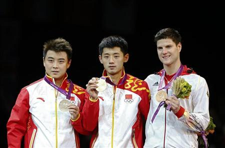 (R-L) Germany's bronze medallist Dimitrij Ovtcharov, China's gold medallist Zhang Jike and silver medallist compatriot Wang Hao celebrate during the medal ceremony of the men's singles table tennis tournament at the ExCel venue during the London 2012 Olympics August 2, 2012. REUTERS/Grigory Dukor