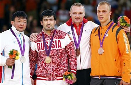 Gold medallist Russia's Tagir Khaibulaev celebrates with silver medallist Mongolia's Tuvshinbayar Naidan (L) anad bronze medallists Germany's Dimitri Peters (2nd R) and Netherlands' Henk Grol (R) during the awards ceremony for the men's -100kg final judo competition at the London 2012 Olympic Games August 2, 2012. REUTERS/Darren Staples