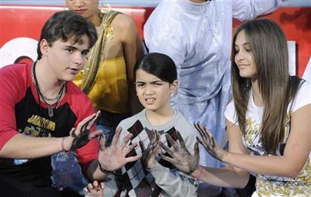 Singer Michael Jackson is immortalized in a ceremony where his children (L-R) Prince, Blanket and Paris use Jackson's shoes and gloves and their own hands to make imprints in cement in the courtyard of Hollywood's Grauman's Chinese Theatre in Los Angeles on January 26, 2012. REUTERS/Phil McCarten
