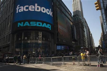 Pedestrians walk near the NASDAQ Marketsite at the start of the listing for Facebook in New York May 18, 2012. REUTERS/Keith Bedford