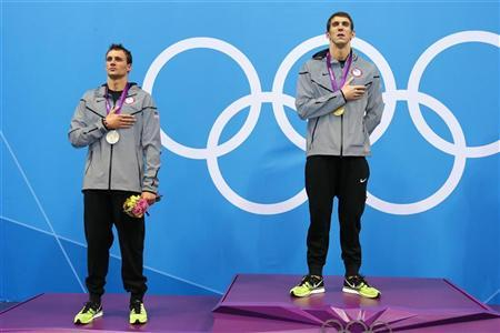 Gold medallist Michael Phelps of the U.S. (R) and silver medallist and compatriot Ryan Lochte listen to their national anthem during the men's 200m individual medley victory ceremony during the London 2012 Olympic Games at the Aquatics Centre August 2, 2012. REUTERS/David Gray