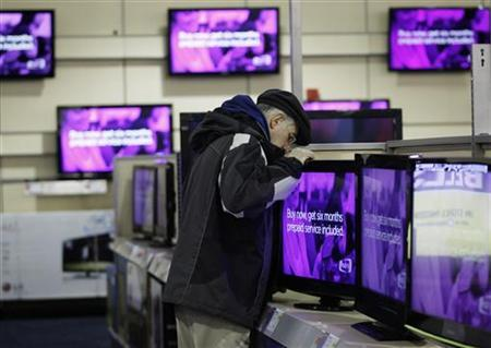 A man looks at a flat screen television at a Best Buy store in Flushing, New York March 27, 2010. REUTERS/Jessica Rinaldi