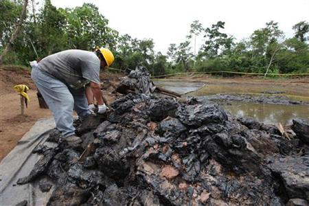 Ecuadorean workers clean up an oil waste pit owned by state petroleum company Petroecuador in Shushufindi, some 410 km (254 mi) east of Quito December 8, 2009. Residents in the country´s Amazon region are suing Chevron, accusing the U.S. company of doing environmental damage while it operated in a consortium with Petroecuadro in the 1970s and 1980s. REUTERS/Guillermo Granja