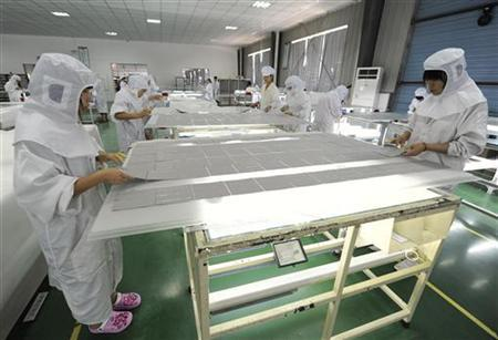 Employees process solar panel components at a solar power plant in Hefei, Anhui province July 26, 2012. China's solar firms warned of a trade war on Thursday, calling on the Chinese government to respond with all means to an anti-dumping complaint filed by European competitors that they said could be a fatal blow. REUTERS/Stringer