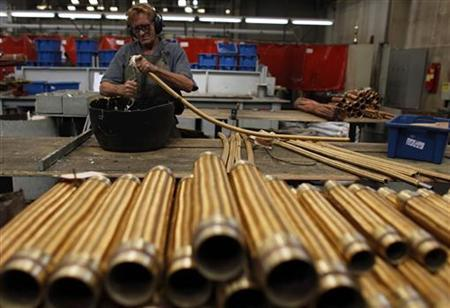 An employee checks a copper hose at the Sociedade Paulista de Tubos Flexiveis (SPTF) metallurgical company which manufactures flexible metal hoses, in Sao Paulo April 20, 2012. REUTERS/Nacho Doce