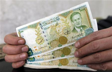 A money changer holds one thousand Syrian pound banknotes, with the picture of late Syrian President Hafez al-Assad, in the border city of Kilis, southeastern Turkey, February 9, 2012. REUTERS/Murad Sezer